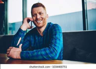 Happy young man with red hair satisfied with good mobile connection in roaming while talking with friends on smartphone device.Positive male communicating on cellular resting in coworking space
