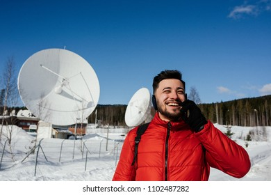 Happy young man in red jacket talking on the cell phone while standing near the radio observatory with big satellite dishes and radio antennas in the forest in winter. Norway