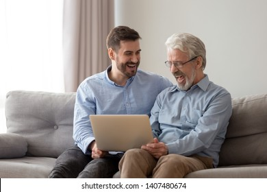 Happy young man relax sit on couch with senior dad have fun watching funny video on laptop together, smiling elderly father and grown son rest on weekend laugh using internet on computer a home