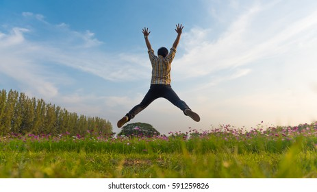 Happy Young man relaxing by Jumping over blue sky in the beautiful flower fields, Holiday Concepts.