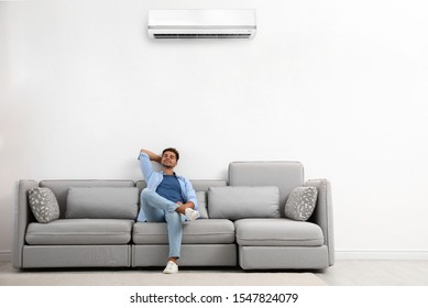 Happy young man relaxing on sofa under air conditioner at home