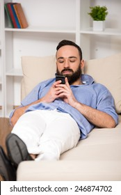 Happy young man is relaxing on sofa and looking at cellphone