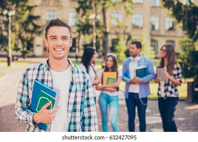 Happy young man rest and holding books while standing on background of university and friends