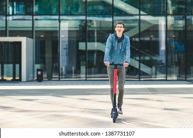Happy young man riding an electric scooter at cityscape background. Ecology transport concept.