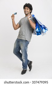 Happy young man with shopping bags and credit card on white.