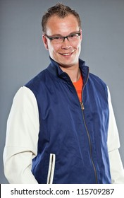 Happy young man with short hair wearing blue baseball jacket and blue jeans. Wearing black glasses. Sportive casual look. Studio shot isolated on grey background.