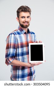 Happy young man showing blank tablet computer screen isolated on a white background