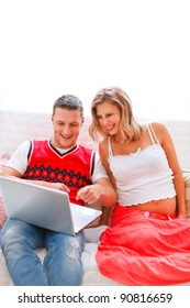 Happy young man showing his pregnant wife something in laptop
