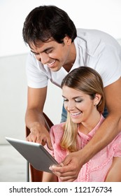 Happy young man showing something to woman on tablet PC