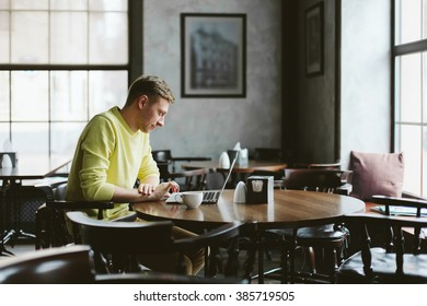 Happy young man sits at a table in an empty cafe with a cup of coffee and working on laptop