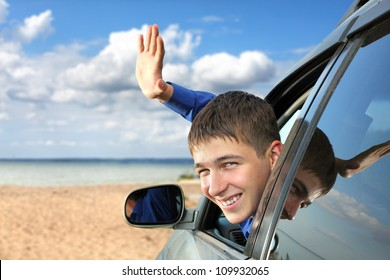 happy young man sitting in the car and wave goodbye
