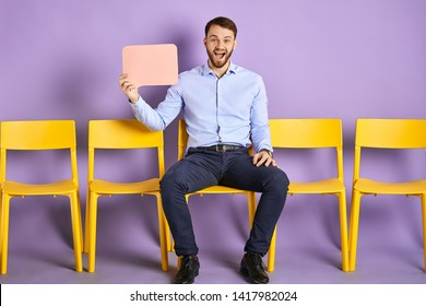 Happy young man sitting on yellow chair and holding up thought bubble waiting for job interview