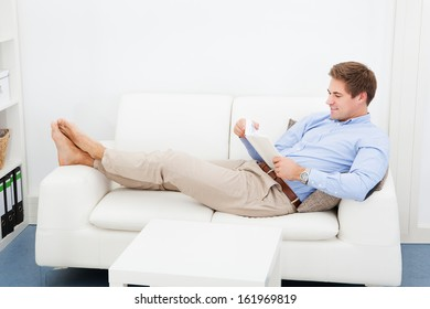 Happy Young Man Sitting On Couch Reading Book