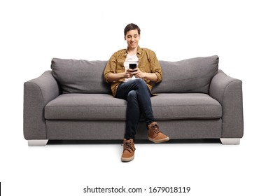 Happy young man sitting on a gray sofa and typing on a mobile phone isolated on white background - Shutterstock ID 1679018119