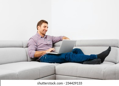 Happy young man sitting on a sofa and using a laptop