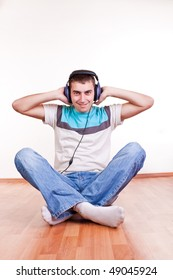 happy young man sitting on the floor with earphones and listening  music