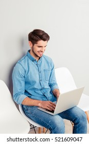 Happy young man sitting on chair and using laptop