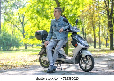 Happy young man sitting on scooter
