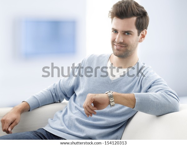 Happy young man sitting on couch at home