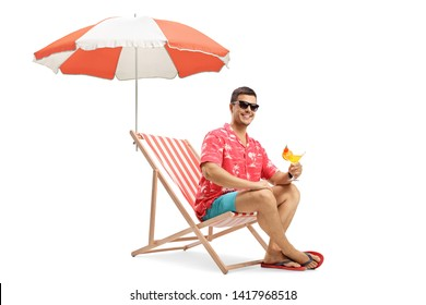 Happy young man sitting under umbrella on a holiday and holding a cocktail isolated on white background