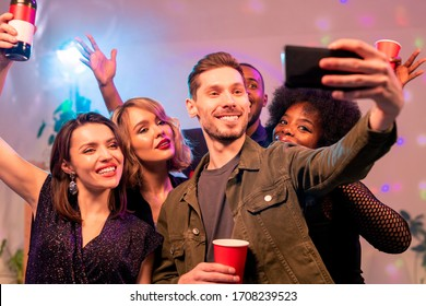 Happy young man with smartphone and three joyful intercultural girls making selfie and cheering up with drinks at home party