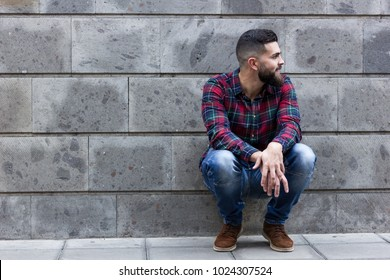 Happy young man squats and leans against wall with smile. Bearded hipster wearing blue jeans and checkers flannel shirt on the street over grey background