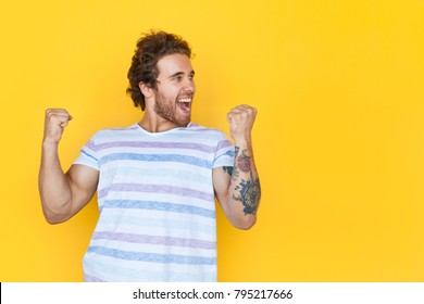 Happy young man standing and celebrating with hands up on yellow background.