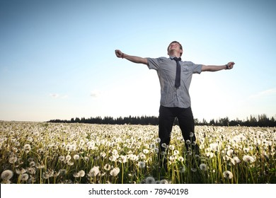 Happy young man standing with raised hands on meadow with dandelions