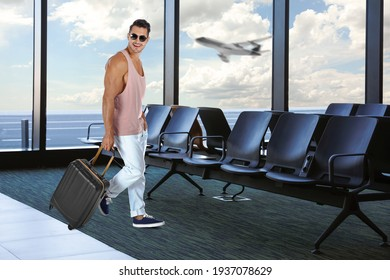 Happy young man with suitcase in airport