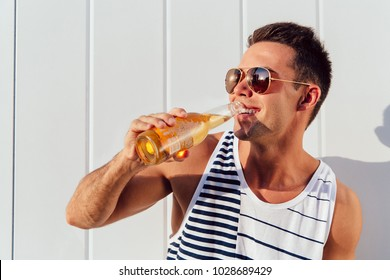 Happy young man in sunglasses drinking cold beer, standing near the wall, outside. Dressed in stylish singlet.