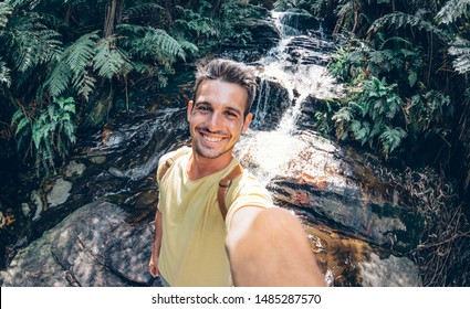 Happy young man take a selfie on a excursion in the forest at summer - Beatiful guy taking a self portrait with his smartphone