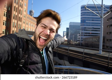 Happy young man taking selfie in the city during his travels
