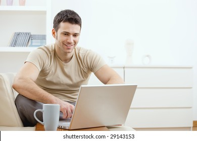 Happy young man in t-shirt sitting on sofa at home, working on laptop computer, smiling.
