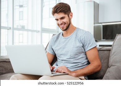 Happy young man in t-shirt sitting on sofa at home. Working on laptop computer and smiling.