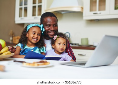 Happy young man with two daughters watching cartoons in the kitchen