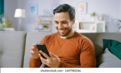 Happy Young Man Uses Smartphone while Sitting on a Sofa at Home. Man Browses Through Internet, Watches Videos and Uses Social Networks at Home.