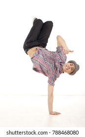 Happy young man wearing casual shirt dancing sitting on one hand, performing breakdance moves on wood floor upside down, with legs up. OK hand gesture and smile. Vertical image in studio on white