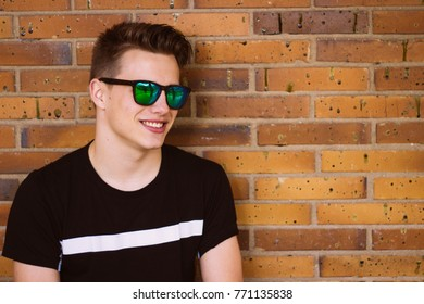 Happy young man wearing sunglasses against brick wall