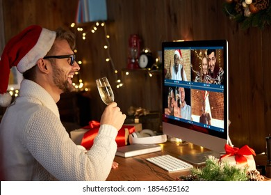 Happy young man wears santa hat drinking champagne talking meeting friends on virtual zoom video call celebrate New Year party in holiday distance online conference chat together on computer at home. - Shutterstock ID 1854625162