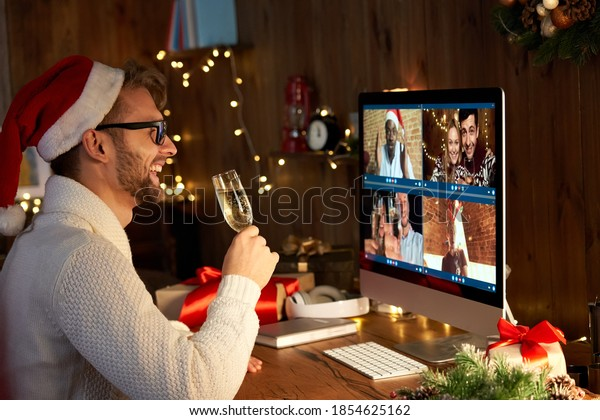 Happy young man wears santa hat drinking champagne talking meeting friends on virtual zoom video call celebrate New Year party in holiday distance online conference chat together on computer at home.