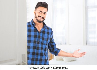 happy young man wears a shirt at his new house front door welcoming people