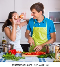 Happy young man and woman cooking vegetables and having fun at kitchen