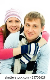 happy young man and woman dressed in warm winter clothes embrace and laugh