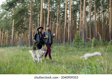 Happy young man and woman having chat while moving along footpath surrounded by pinetress in park or forest