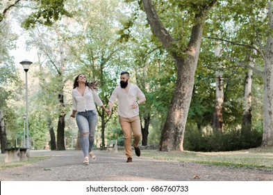 happy young man and woman holding hands and running in park, healthy recreations for fat people, full body of two person who feeling free in park, love and togetherness concept