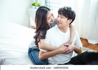 Happy young man and woman hugging embracing indoors. Portrait close up smiling husband and wife piggyback ride at apartment and looking each other.