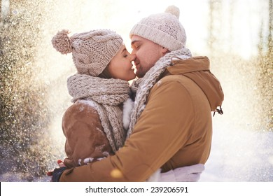 Happy young man and woman kissing in snowfall