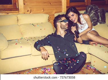 Happy young man and woman singing karaoke on glamorous party together.