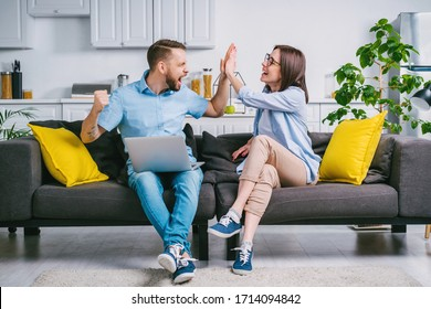 Happy young man and woman sitting at home on comfortable sofa with their laptop computer, celebrating money win in online lottery giving high five to each other.