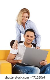 Happy young man and woman sitting together and looking at computer screen